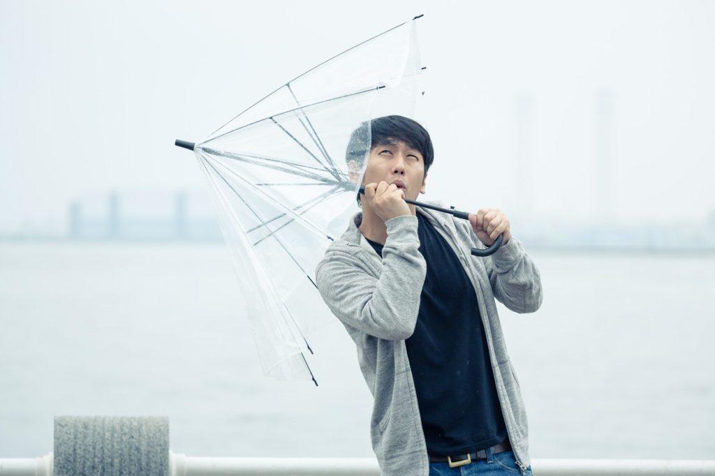 強風で傘が飛ばされそうな男性