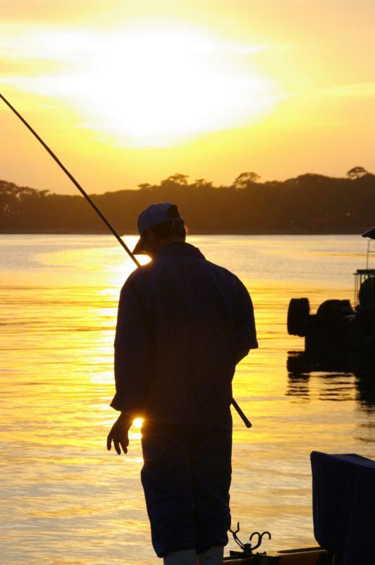 夕くれに釣りをする人